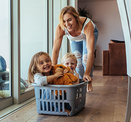 mother pushing kids in laundry basket
